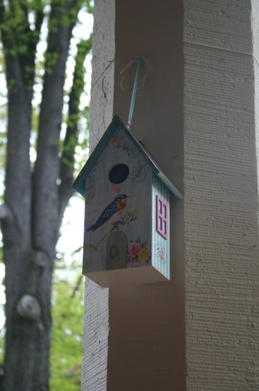 Buntes Vogelhaus hängt an einer Steinsäule