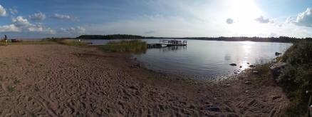 Sandstrand mit Holzsteg und blauem Meer.